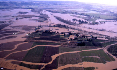 Aerial view of farms along a river with flood waters in fields and around buildings