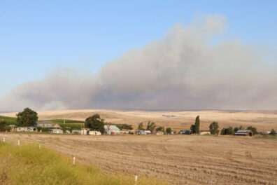 Plowed fields and farmhouses, with billowing smoke in the distance