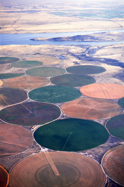 Aerial view of green and dry center pivot circles with the Columbia River in the background