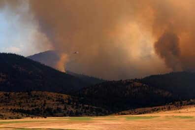Open fields transition to forested hillsides, with two large smoke plumes and dense smoke across the landscape. A firefighting plane crosses in front of the smoke