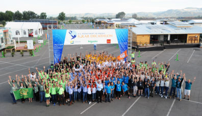 Teams cheer in front of the 'Solar Decathlon Village' during the Opening Day of the U.S. Department of Energy Solar Decathlon at the Orange County Great Park, Irvine, California Thursday, Oct. 8, 2015. (Credit: Thomas Kelsey/U.S. Department of Energy Solar Decathlon) There are many students and staff members all clusered around the opeing sign. Each is wearing a team shirt that has their colors on it creating a rainbow of shirts. Used on the EnCity Website.