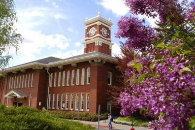 This is an image of the Bryan clock tower on the Washington State University Campus. The clock tower is a red brick color with white trim and at the edge of the image are a group of lavendar flowers. Used on the EnCity Website.