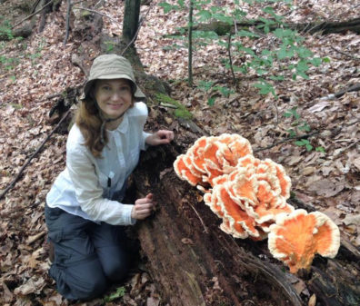 Professor Tanya Cheeke, soil microbial ecologist, kneels in a forest beside a large, orange fungus growing in an old log.