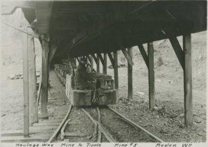 Photo of a man in a mining car on tracks under a wooden structure