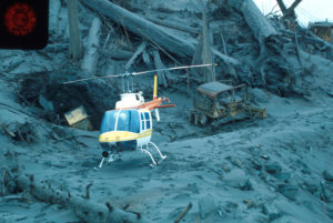 Photo of a helicopter resting on volcanic ash, with felled trees and partially buried construction equipment in the background