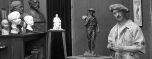 Picture of artist Alonzo Victor Lewis in studio, including several busts and a model military statue