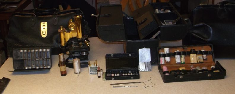 Photo of various old medical supplies, medical bags, and a microscope