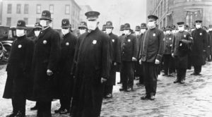 Uniformed policemen wearing gauze face masks stand in lines on a Seattle street.