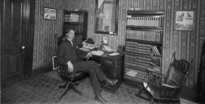 photo of Doc Wright sitting at a desk n his office, circa 1906