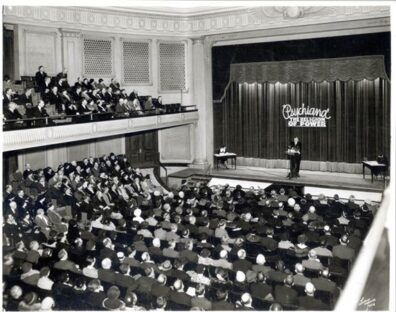 Psychiana leader Frank Robisnon on stage speaking before a large audience