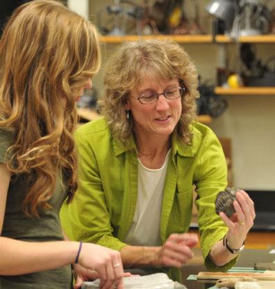 Professor Lisa Carloye shows a student a biological specimen.