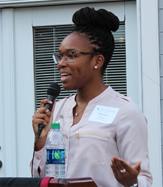Marissa Chukwu delivering a speech with a microphone in hand.