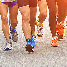 group of individuals running on road, shows only legs and feet in running gear