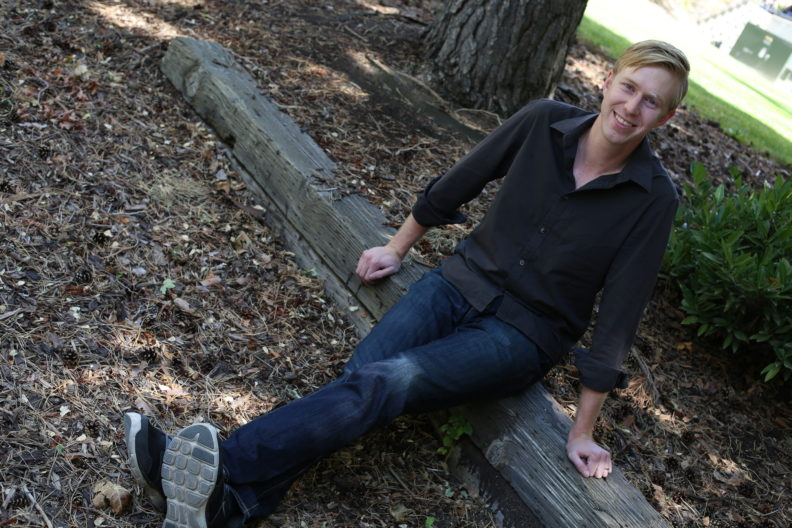 Dustin Van Orman sitting on the ground while smiling upward at the camera.