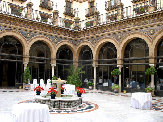 """SEVILLA: It had taken us much longer to get to the rendezvous with our guide in Córdoba than we had expected, so we set out early the next day for Sevilla, but that turned out to be a much shorter and easier trip, so we were quite early. We decided to treat ourselves to the lavish breakfast buffet at the Hotel Alfonso XIII and enjoyed looking out at the covered courtyard of this fantastic building, erected in 1929 but redolent of much earlier eras. (The city is usually called """"Seville"""" in English, but we preferred to go with actual Spanish place names.)"""