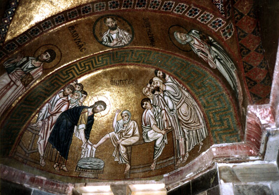 OSSIOS LOUKOS: Mosaic in the main sanctuary depicting Christ washing the feet of the disciples. The heavy outlining and gold background are typical of the Byzantine style. The flash surreptitiously used in this shot (the church was deserted) illuminated Christ's head.