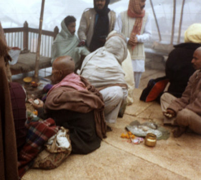 """This Brahmin priest takes the ashes brought to him by bereaved survivors and kneads them into balls with Ganges water which are then thrown into the river, bringing merit to the deceased spirit comparable to that of being cremated on the """"burning ghats"""" themselves. Shot on a chilly, foggy winter morning."""