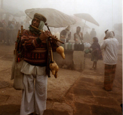 This vendor of musical instruments demonstrates his wares on a cold, foggy winter morning, at the top of the bathing ghats of Varanasi.