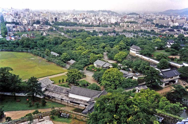 KYOTO: View of the castle grounds from the topmost tower, with the women's quarters in the long, low building on the right. Modern Himeji city in the background. May 25, 1998