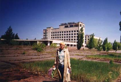 To my right is 'Palace' Square. Behind my back is a hotel (where my son and I, by invitation of the nuclear station, lived the first half year), behind it--the building of the former City Committee of the CPSU, where after the explosion of Reactor 4 of the ChAES [the Chernobyl Nuclear Energy Station] the government commission spent almost two days [and nights] deciding what to do with the inhabitants of Pripiat.