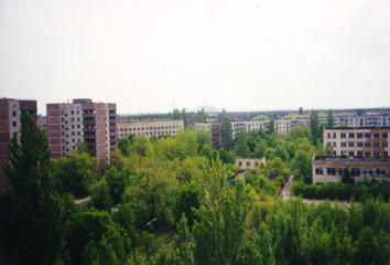 Sasha's former school is the two-story building on the right; in front of the school there is football field overgrown with young trees. The reactor dimly visible on the horizon. (May, 9, 1999)