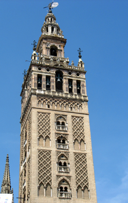 """SEVILLA: The famed bell tower of the Sevilla Cathedral is composed of a Christian campanile built on top of a Moorish minaret (built 1184-1196). The sculpture on top, a figure depicting Faith, veers about with the wind, giving the tower its name: """"La Giralda."""""""