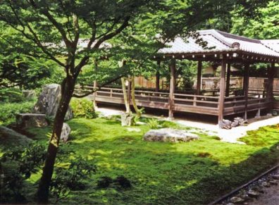 KYOTO: View across a moss garden from one wing of the temple to another. Like other temples, this was originally built as a villa, for the retired Emperor Kameyama; but upon his death in 1291 it was converted to religious uses. Emperors used to be required to retire upon the birth of an heir, which kept the imperial family safely weak and led to a large leisured class of reasonably young retirees. The present buildings are a 17th-century reconstruction, the headquarters of the Rinzai school of Zen. May 26, 1998