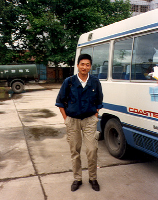 "XIAN: Our local guide in Xian, friendly and well-liked. Also quite tall. In front of our bus, one of several uncomfortable (though sometimes air-conditioned) ""Coasters"" that we did our traveling in."