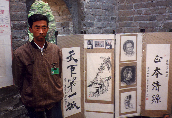 GREAT WALL: Artist at the great wall, displaying drawings of Margaret Thatcher & Sylvester Stallone.