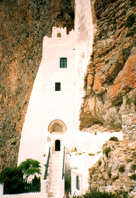 AMORGOS: The stairwell narrowed by the cliff face curving into it.