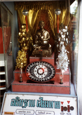 This device contains a statue of the Buddha and electric joss sticks which, when a coin is inserted, generate a lucky number for the worshiper to use when buying a lottery ticket.