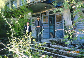 Sasha & a former schoolmate at the entrance to the same school, now abandoned and overgrown. (April, 26 1999)
