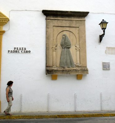 VEJER DE LA FRONTERA: Vejer was noted for centuries for its enveloping female garb, which left only one eye uncovered. The woman walking by this plaque memorializing the tradition illustrates typical modern dress.