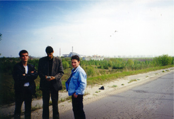 Sasha Sirota with his friends on the road from Pripyat to Chernobyl, with the reactor visible in the background.