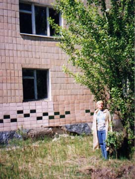 "In Microregion 1; after the accident this was one of the ""dirtiest""--that is, one of the most radioactive--areas. I am standing by my apartment house. On the second floor is a window to our apartment. In 1986, there was no poplar by this building; rather, there was a little twig that Sasha had planted that spring. Our children played here during the night and morning of April 26-27, 1986. And closeby is the road, along which the cars were rushing to the station and back."