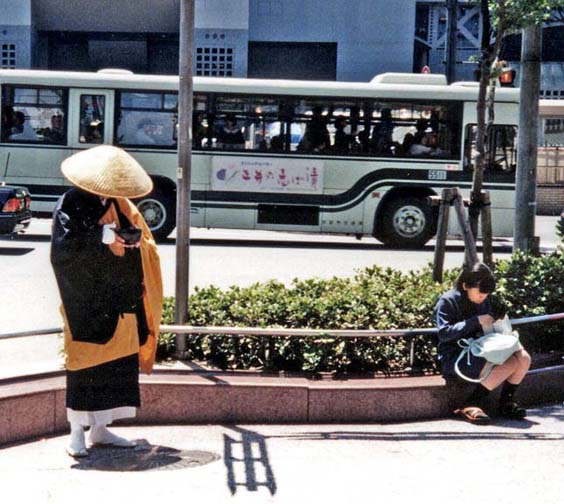 KYOTO: Buddhist monks are supposed to make their entire income from begging, but their begging style is very passive. The hat tilted down to cover the monk's face as he chants on this street corner prevents him from appealing for donations with his eyes. He remains entirely passive, relying on the good will and piety of passersby. May 13, 1998.