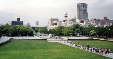 """HIROSHIMA: View of the grounds of the Hiroshima Peace Park, site of the world's first atomic bombing (August 6, 1945). Brick crumbled, people evaporated and were burned, and the wood and paper houses were incinerated. Resistance was strong for many years to creating the park, but it is now a center for world peace activities. From the balcony of the museum, facing toward the memorial arch. Rear center is the """"peace dome""""--the concrete and steel exhibition hall that was directly under ground zero. Just to its left is a huge baseball stadium. In the background, modern Hiroshima. May 17, 1998"""