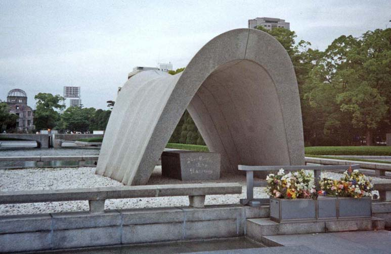 """HIROSHIMA: This monument, The Peace Arch, lists all the names of the known victims. It is acknowledged that for decades the enslaved Koreans who died were ignored at the site; but their deaths are now honored alongside those of their captors. In the background at left, the """"atomic bomb dome."""" May 17, 1998"""