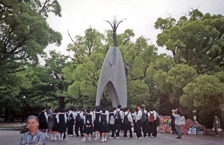 HIROSHIMA: A school group in front of the monument to Sadako, the girl who began the tradition of folding paper cranes. She hoped to regain her health and failed; others imitate her as a symbol of their desire for peace. Note the draped strings of colored paper cranes at right. May 17, 1998