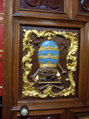 ARCOS DE LA FRONTERA: Detail from church door showing a skull wearing a mitre.