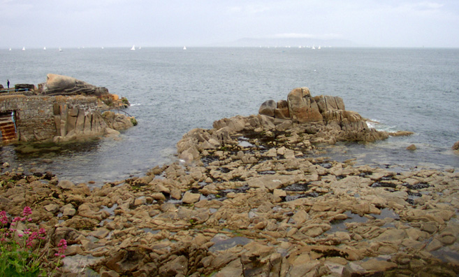 "SANDYCOVE: Looking out to sea, Joyce would have seen these rocks adjacent to the natural ""Forty Foot Pool"" where the characters in his novel go swimming, and which is still a swimming spot today."