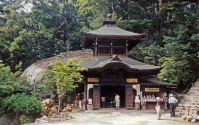 """MIYAJIMA: This is the first major temple on the way up Mt. Misen. In it a pot that is reputed to have been boiling steadily ever since the monk Kobo Daishi (774-835) used it to boil his dinner: sort of a variation on the """"eternal flame"""" theme. Note the supply of firewood on the left. He is reputed to have invented the classic Japanese rice paddle, so such paddles are sold throughout the island as souvenirs. May 18, 1998"""