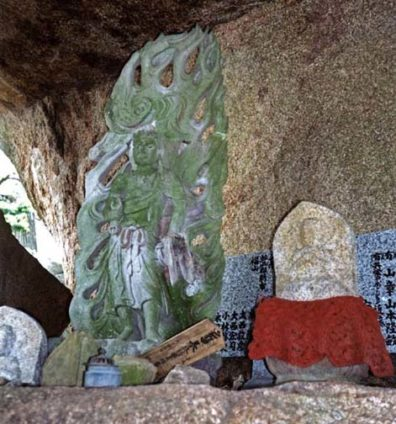 MIYAJIMA: The top of Mt. Misen is littered with huge, remarkably shaped stones, some of which shelter images like this one. Note the crocheted bib on the right-hand image of Jizo, Buddhist saint and protector of children. It is traditional for parents seeking help for an ailing child or hoping to improve its lot after death to dress a Jizo statue in a red bib. May 18, 1998
