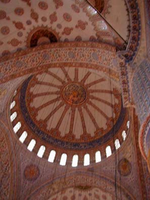 BLUE MASQUE: The interior of the great dome. The vertical wires support the lamps. The space is luminous, open. Despite its imposing size, the interior of the Blue Mosque gives a great impression of clarity. The rich ornamentation doesn't encrust it like some 17th-century European churches, but embellishes its grand, noble lines.