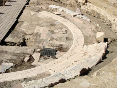 MALAGE: Closer view of the ancient stage area. The strips to the left make up a modern metal stage on which performances are held. Málaga had been settled in this area by Phoencians some time in the 7th century; but the Roman theater was built in the early years of the reign of Augustus.