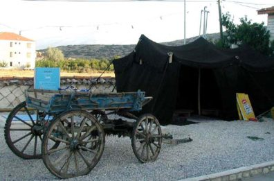 PHASELIS: At another bus stop we spotted this ethnic exhibit: a gypsy cart and traditional tent. Blue plastic seems to be modern equivalent for the migrant workers (mostly women) we saw picking cotton in the fields. Note the ad for Lipton tea.
