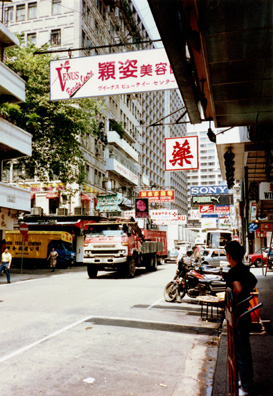 I bought some Hong Kong CDs of Chinese music cheap, we browsed through a nice bookstore, walked down to the harbor, and ate late at a Chinese restaurant: barbecued duck and goose. Right: Hong Kong street by daylight on May 15, a hot and muggy day.