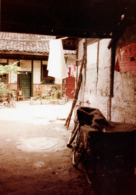 CHENG:DU Typical Cheng Du residential courtyard, set back from the street, with bamboo chair in front of the door.