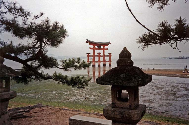 MIYAJIMA: This torii, anchored firmly in the tidal flats just offshore from the Itshukushima Shrine, is a famous symbol of Japan, seen here at sunset, and low tide. May 18, 1998