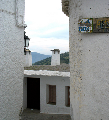 """LAS ALPUJARRAS: The sign directs visItors to the wonderful """"Ibero"""" restaurant. Note the capped chimneys typical of this region. They are a local trademark."""